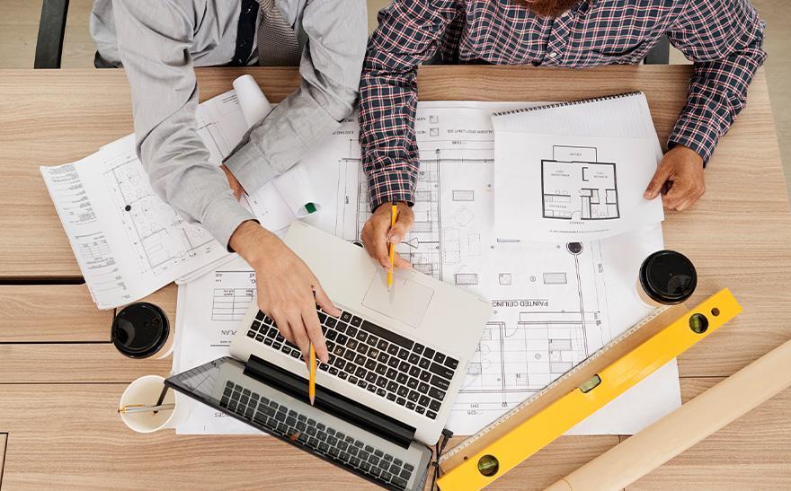 dwie osoby dyskutują nadplanami budowlanymi